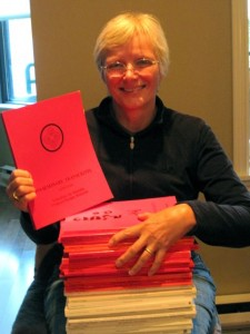 Acharya Judy Lief displaying all the seminary transcripts