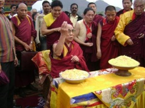His Holiness leads the traditional throwing of rice, seated before the entrance to the new monastery, as part of the bestowing of blessings.