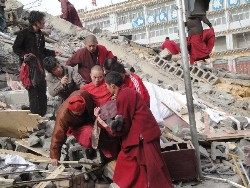 Xinhua photo shows a monk being helped out of rubble.