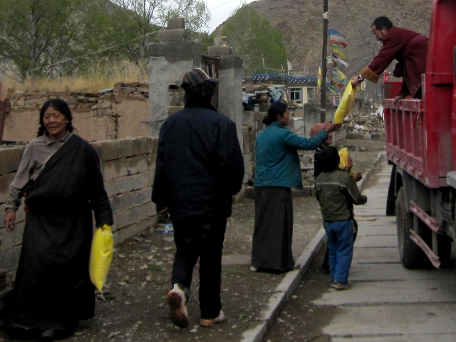 Surmang monks distribute tsampa flour, the staple diet for Tibetans.