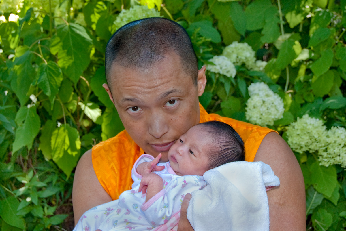 The Sakyong holding Jetsun Drukmo in the court gardens on the day she was one week old.
