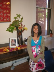Emma Hessey stands next to photo of Kyoko Kita, Sensei at Harvest of Peace in Boulder