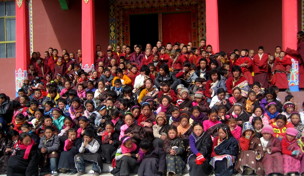 School children seated on the steps of the Surmang Shedra.