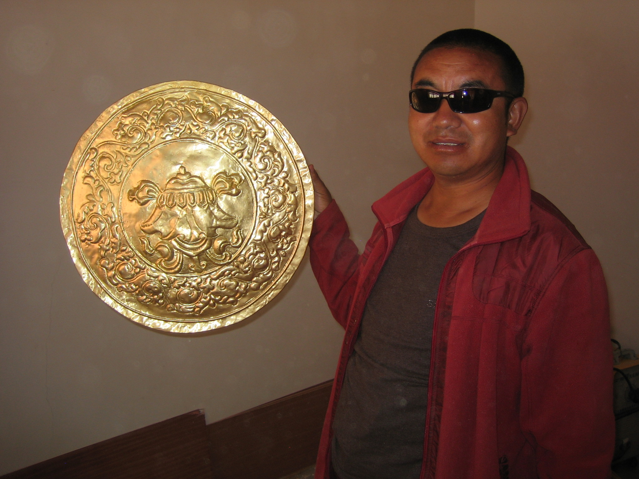 Surmang Khenpo holds up one of the golden medallions.