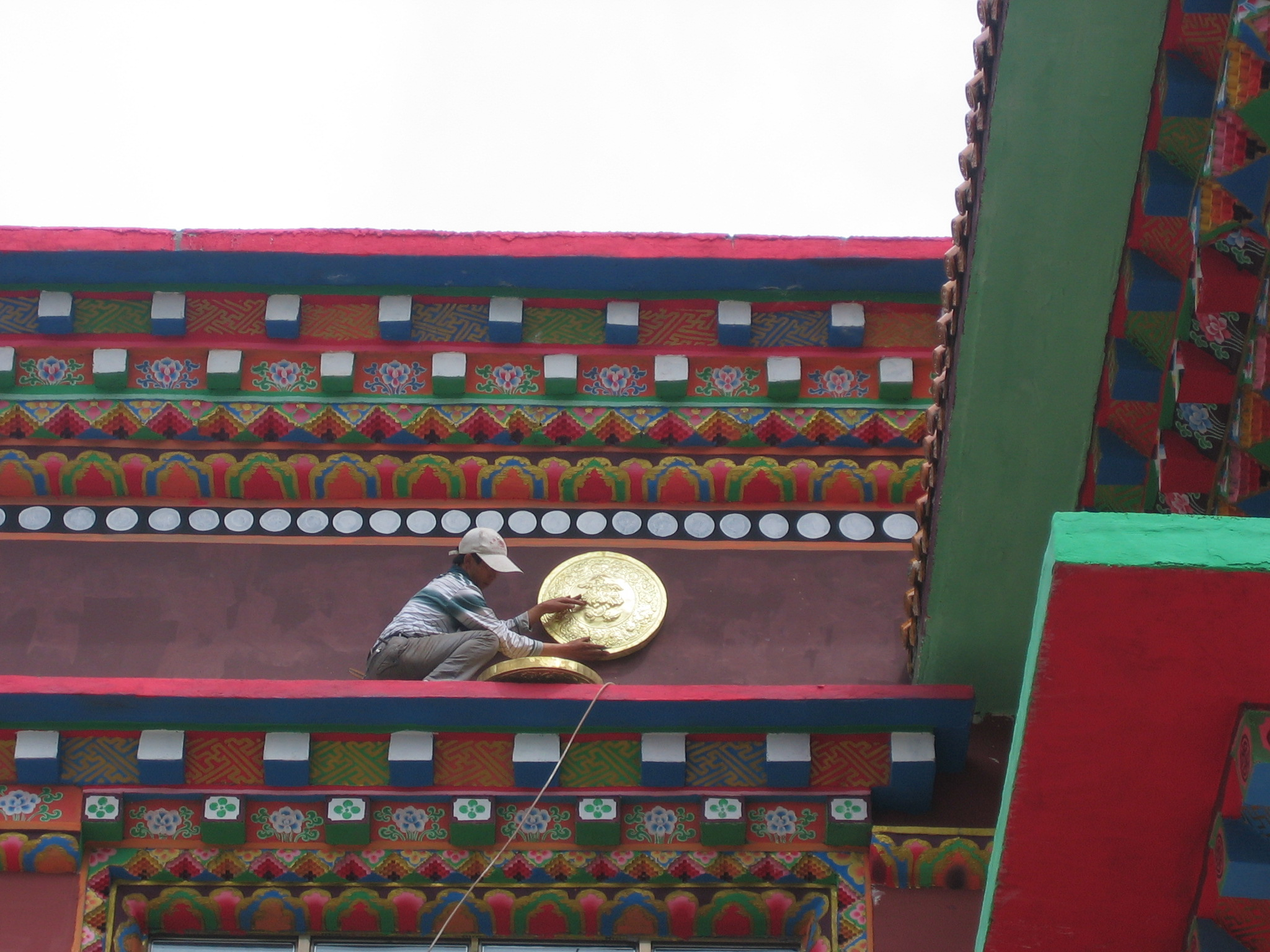 Worker mounts the first medallion while perched precariously on a ledge.