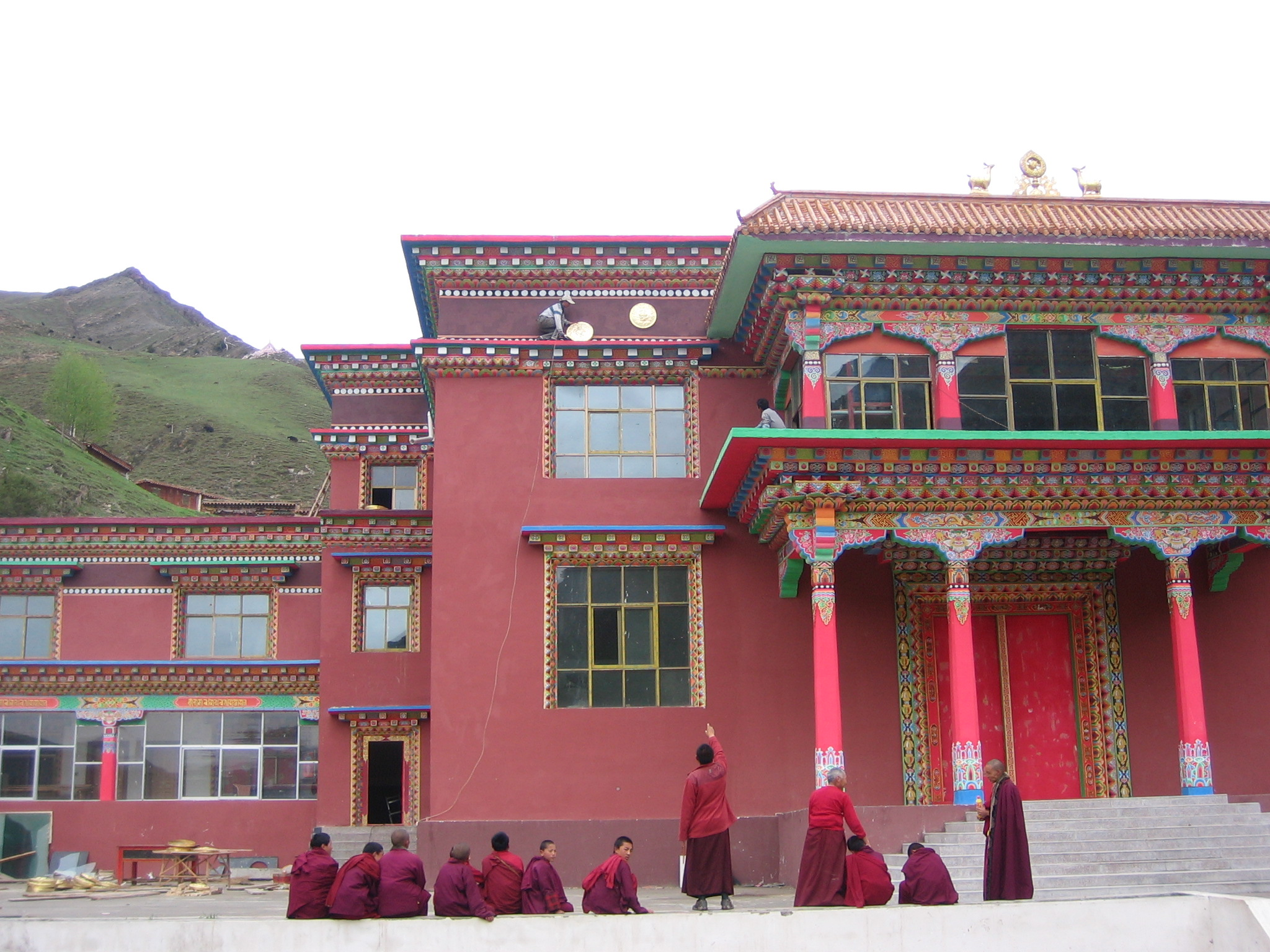 From below, Khenpo points to the right spot to place the medallion.