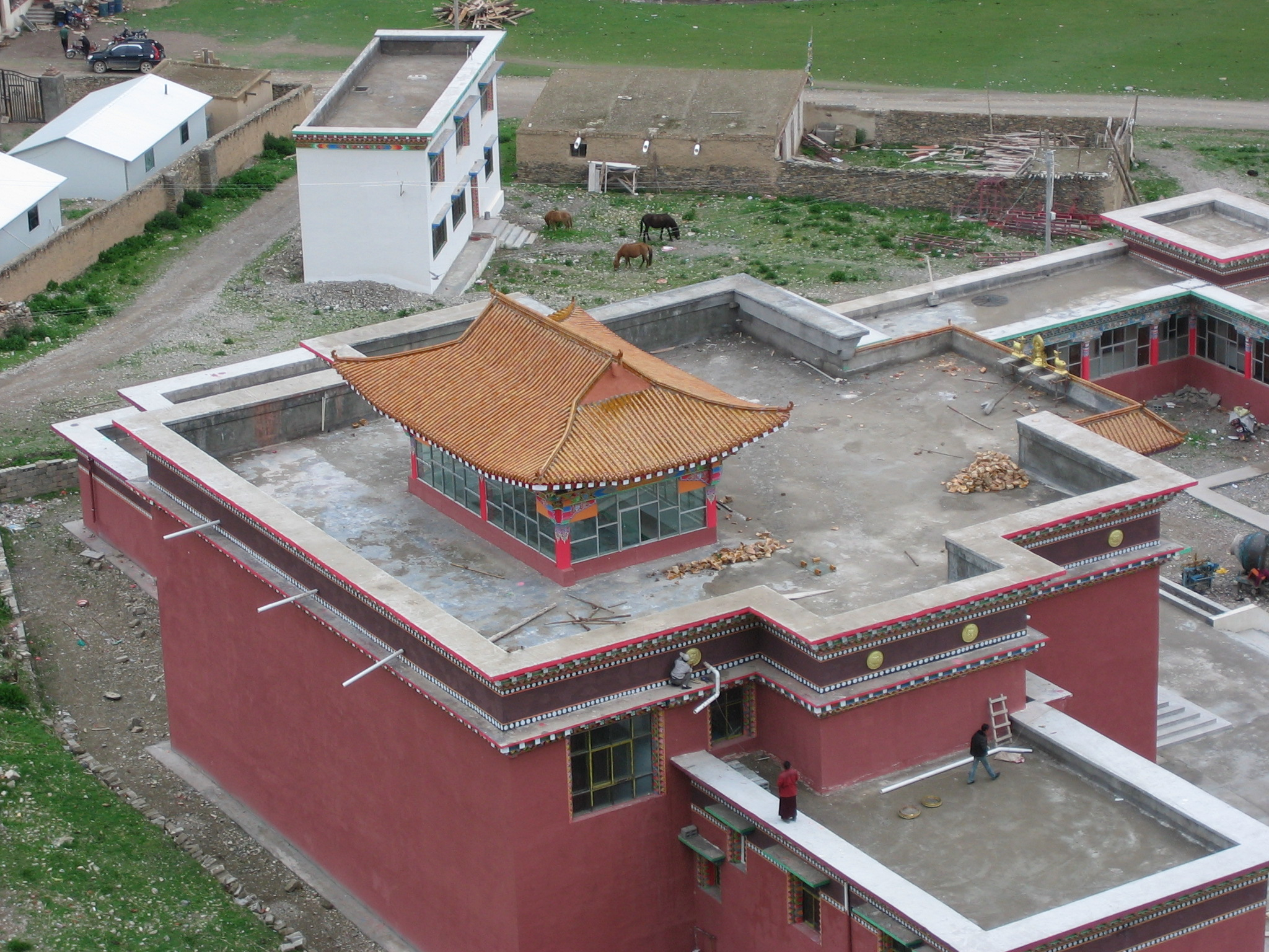 Khenpo supervises from the roof as medallions are installed along the side of the shedra.