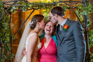 Sarah Kimball and James Hudspeth kiss their Officiant - Sarah Lipton