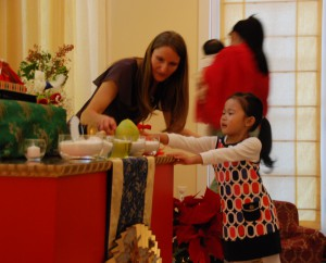 Jetsun Drukmo places an offering on the Children's Day shrine with help from Amanda Betzen.