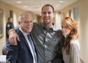 Going home at last: Ebola survivor Ashoka Mukpo, an NBC freelance cameraman, poses with his father, Dr. Mitchell Levy and his partner Helen Finlay after being discharged from a special unit at the Nebraska Medical Center in Omaha, Nebraska on Wednesday, photo courtesy of Reuters and the Daily Mail
